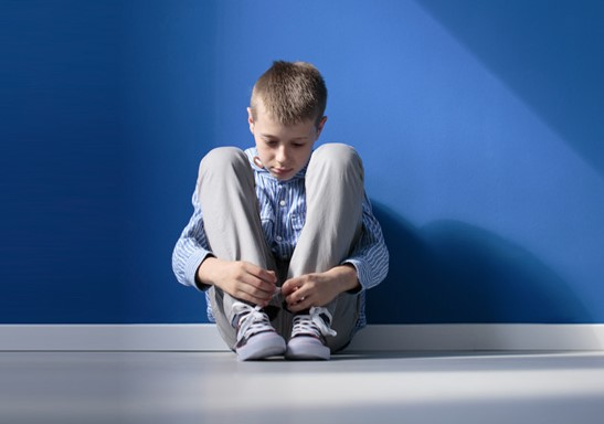 Boy sitting on the floor, sad