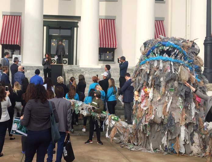 A 'monster' of plastic litter stands outside Florida's historic capitol as Catherine Uden, Southast Florida campaign organizaer for Oceana, calls on lawmakers to reduce plastic waste. Photo: Laura Cassels
